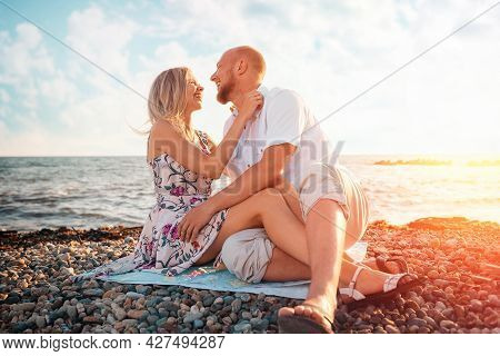 Summer Picnic. Pretty Couple Of Caucasian Man And Woman Sitting At The Beach. Romance Vacation.