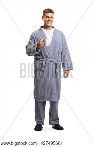 Full length portrait of a young man in a bathrobe holding a cup isolated on white background