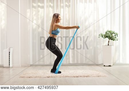 Full length profile shot of a woman exercising with an elastic rubber band at home