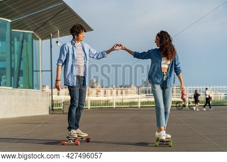 Romantic Man And Woman Ride Longboard Holding Hands Show Heart With Fingers. Cute Trendy Couple In L