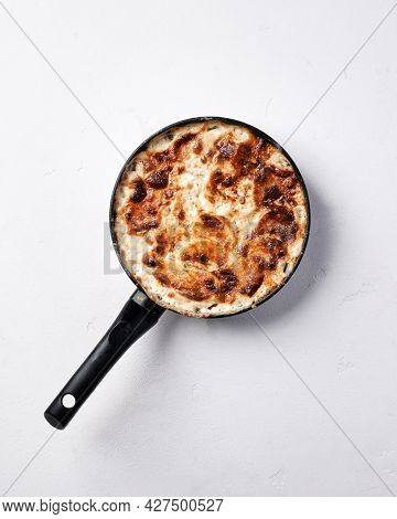 Potato Gratin In A Frying Pan On A White Table. Top View