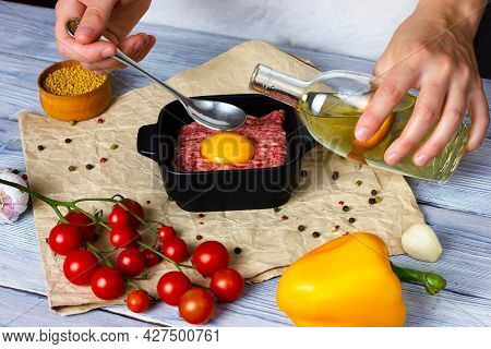 The Process Of Cooking Cutlets On A Light Wooden Table From Minced Pork. Female Hands Sprinkle Seaso