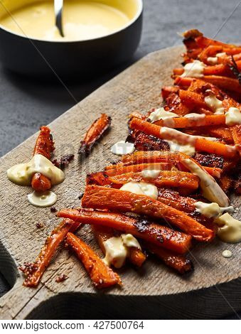 Sliced Caramelized Carrots With Parmesan Lie On A Cutting Board. 45 Angle View