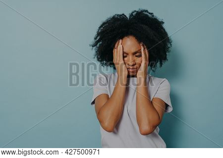 Tired Stressed Young African Woman In Tshirt Holding Head In Hands And Keeping Eyes Closed, Sighing