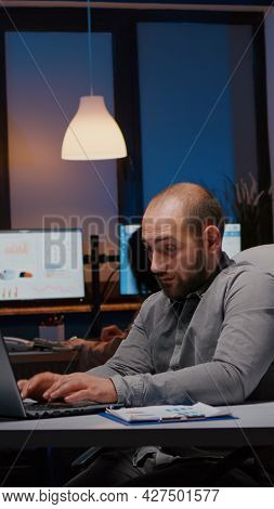 Overworked Businessman Typing Management Strategy On Laptop Working In Startup Company Office Late A