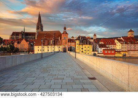 Regensburg, Germany. Cityscape Image Of Regensburg, Germany With Old Stone Bridge Over Danube River