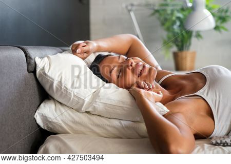 Happy Woman Waking Up Stretching Arms On The Bed In The Morning