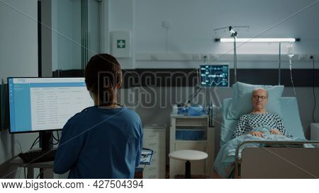 Nurse Examining Medical Results On Computer For Patient Laying In Hospital Ward Bed. Sick Old Man Wa