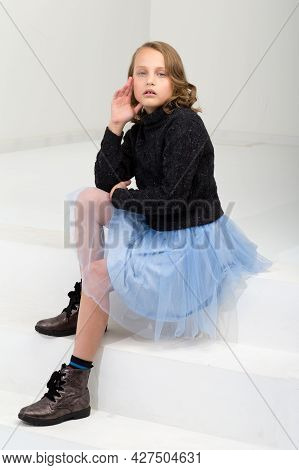A Beautiful Girl In A Black Jumper And A Blue Fluffy Skirt Sits On A White Staircase. Pretty Blonde