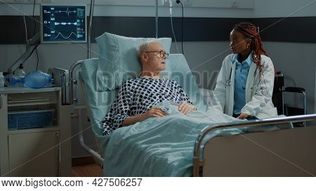 African American Doctor Talking To Sick Elder Patient In Hospital Ward At Clinic. Old Man Getting Co