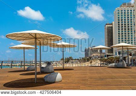 Sun umbrellas and high-rise hotels on the promenade along the shore of Mediterranean sea in Tel Aviv, Israel.