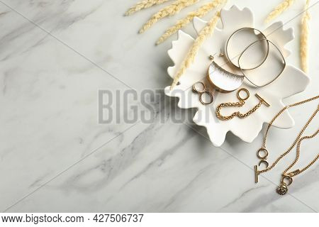 Different Elegant Bijouterie And Plate On White Marble Table, Flat Lay. Space For Text
