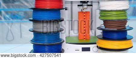 ABS and PLA filament next to 3D Printer. Plastic   coils