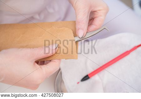 A Master In A Beauty Salon Pulls Out Sterile Tweezers From A Craft Bag For Electro Epilation