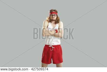 Funny Nerd In Gym Shorts, Tank Top, Headband And Glasses Pretending To Be Tough Guy