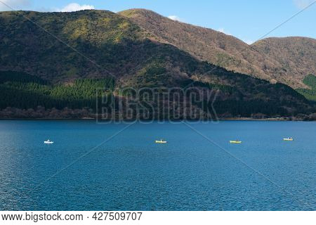 Small Fishing Or Tourists Boats Floating In Row In The Sea,on Large Mountain Background Covered With