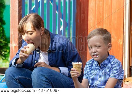 Preschooler Boy With Mom Eating Ice Cream On The Porch Of A House In The Village On A Summer Sunny D