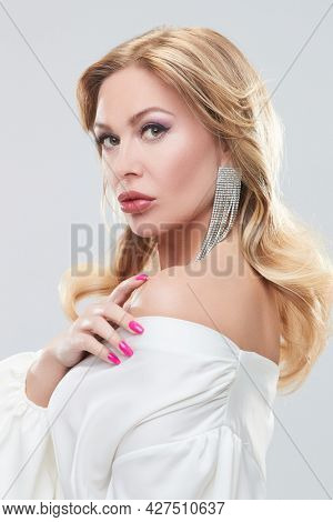 Beauty and jewelry. Beautiful sexy middle aged woman with enlarged full lips and evening makeup posing in precious jewelry. White background.
