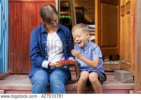 A Six-year-old Boy With His Mother Is Eating Fresh Fragrant Raspberries In The Village Outdoors On T