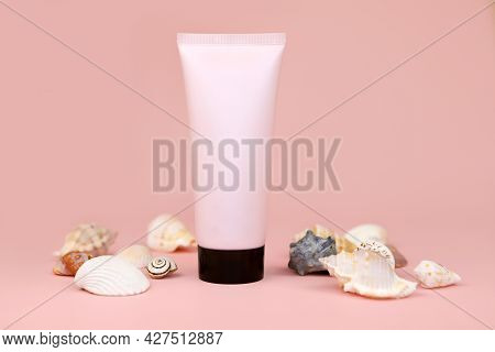 Unbranded Pink Squeeze Bottle Cream Tube With Black Screw Cap  And A Lot Of Seashells On Pink Backgr