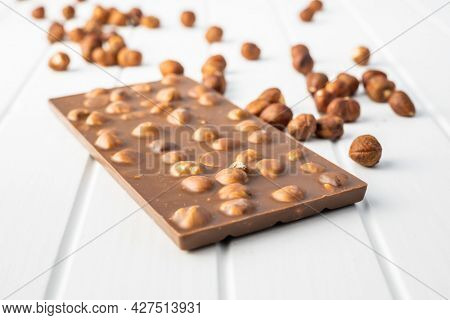 Chocolate bar with hazelnuts on white table.