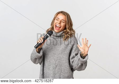 Image Of Happy Blond Girl In Grey Sweater, Singing With Microphone, Standing Over White Background