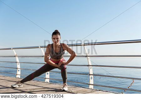 Young Attractive Sportswoman Workout Near The Sea. Fitness Woman Stretching Her Legs Before Jogging