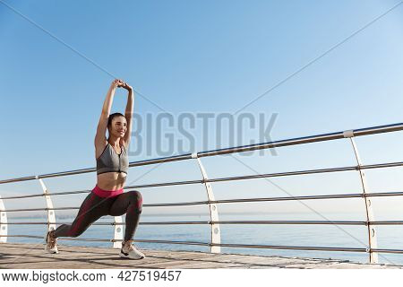 Low Angle Shot Of Healthy Attractive Fitness Woman Stretching Legs And Hands, Workout Alone Near The