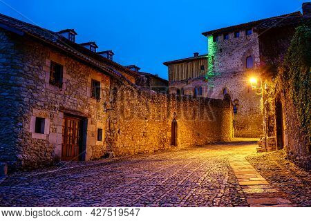 Picturesque Medieval Town Street With Cobbled Street And Church Tower At Dusk. Santillana Del Mar.