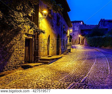 Picturesque Old Stone Town Street With Street Lamps At Dusk. Santillana Del Mar.