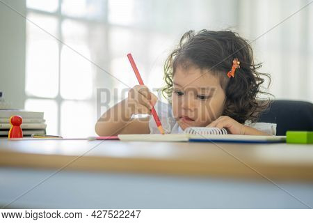 Little Girl Sits At The Table And Draws On Paper With Colored Pencils, Children Education.