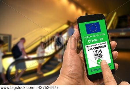 A Man In A Shopping Mall Holds A Smartphone With The European Union Digital Green Pass For Covid-19