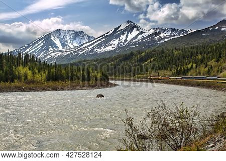 Train Crossing The Alaskan Frontier Back Country, Passing Mountain Peaks And Flowing Rivers.