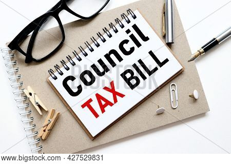 Council Tax Bill. Text On Paper, On A Notebook On A Craft Background, Near Glasses