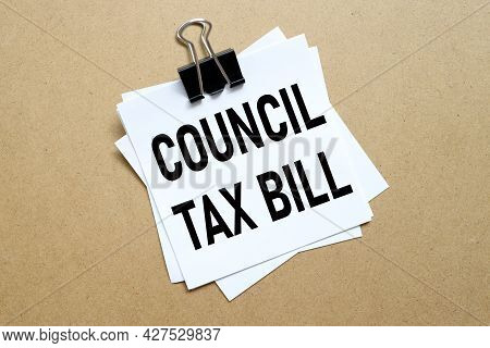 Council Tax Bill, The Paper Is Clamped With A Clerical Clip. Paper On Wood Background.