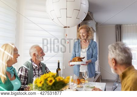 Two Senior Couples Gathered Around Table, Celebrating Thanksgiving, Having Dinner Together At Home,