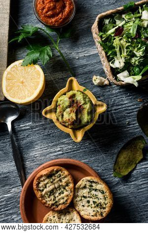 high angle view of a yellow ceramic bowl with some guacamole on a gray rustic wooden table, next to some toasted bread, some chopped lettuce and a bowl with some vegan sobrasada, made with almonds