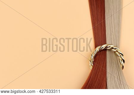 Tails Of White,red Hair Are Strung On A Golden Ring On A Delicate Background.the Concept Of Hairdres