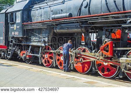 Worker Checks A Black Retro Steam Locomotive At Railway Station