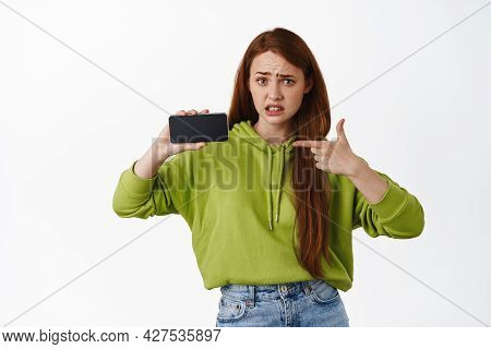 Portrait Of Girl Points At Phone Screen With Concerned And Disappointed Face, Have You Seen This, Sh