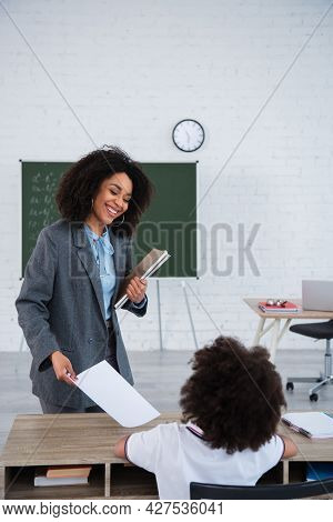 Positive African American Teacher With Notebooks Giving Paper To Pupil In Classroom