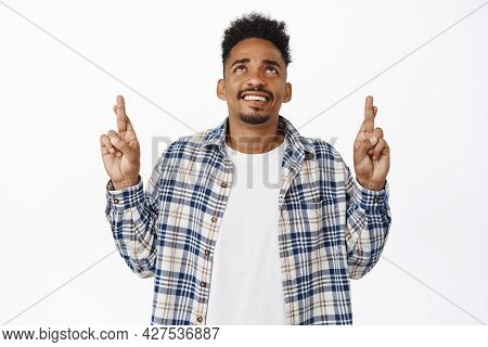 Hopeful African American Man Smiling, Hold Finger Crossed And Looking Up, Making Wish, Waiting For G