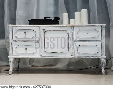 A White Retro Commode With A Music Player And Candles Standing On It. Interior Decor