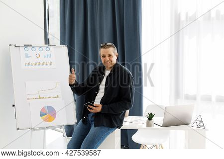 A Man Dressed In Casual Clothes Works In The Office And Holds A Mobile Phone