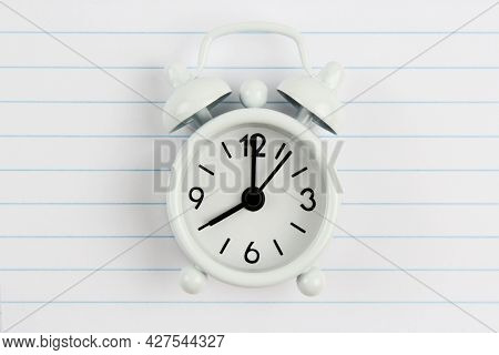 Back To School.on The Background Of A Notebook Sheet In A Ruler Is An Alarm Clock With A Place For T