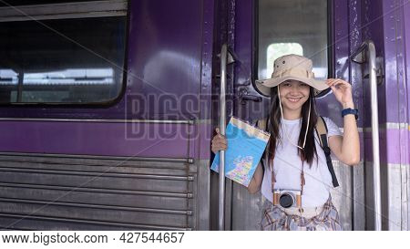 Happy Smiling Asian Woman Travelers Looking At Camera On The Door Of The Train With Backpack, Touris