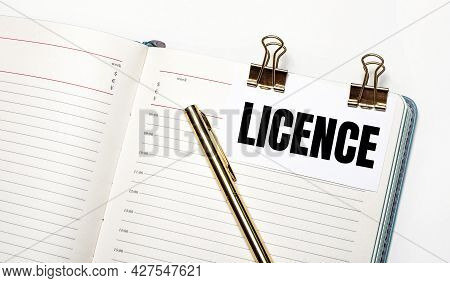 On A Light Background, An Open Notebook, A Sheet Of Paper With Gold Clips And The Text Licence And A