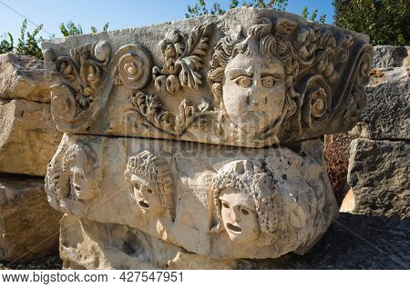 Theatrical mask and face stone relief of ancient town of Myra in Lycia, Ruins of ancient city of Myra in Demre, Turkey