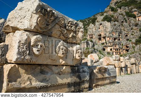 Ruins of ancient city of Myra in Demre, Turkey. Theatrical masks and faces relief and ancient rock tombs in Lycia region