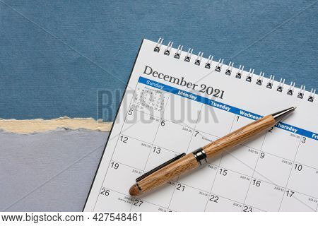 December 2021 - spiral desktop calendar against abstract paper landscape with a stylish pen, time and business concept